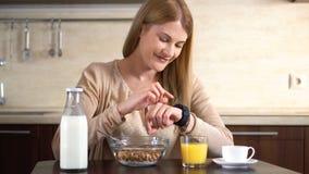 Härlig attraktiv kvinna som har frukosten, genom att använda hennes smarta klocka Bläddra internet Läs- nyheterna stock video