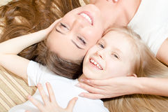 Härlig attraktiv moder eller syster med den liggande framsidan för barnflicka - till - le för framsida lycklig & seende kamera Royaltyfri Foto