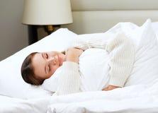 Härlig attraktiv ung europeisk lyin för kvinnabrunettmorgon royaltyfri foto