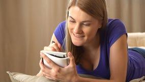 Härlig attraktiv ung kvinna i en violett t-skjorta handstil i en anteckningsbok Framställning av en lista och att tänka och le stock video