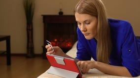 Härlig attraktiv ung kvinna som ligger på soffan och direktanslutet köper något med kreditkorten 00327 lager videofilmer