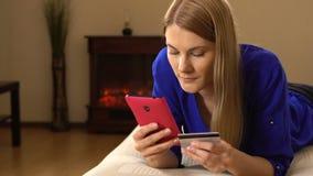 Härlig attraktiv ung kvinna som ligger på soffan och direktanslutet köper något med kreditkorten 00325 stock video