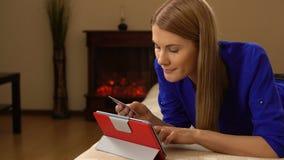 Härlig attraktiv ung kvinna som ligger på soffan och direktanslutet köper något med kreditkorten lager videofilmer