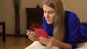 Härlig attraktiv ung kvinna som ligger på soffan och direktanslutet köper något med kreditkorten stock video