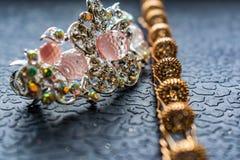Härlig automatisk hårspänne med skinande stenar och rosa pärlor på mörk texturerad bakgrund Guld- hårnålar med vita bergkristalle arkivfoto