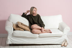 härlig avslappnande sofatröjakvinna royaltyfria foton