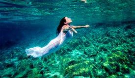 härlig avslappnande vattenkvinna arkivfoto