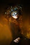 Härlig bärande karnevalmaskering för ung kvinna med fjädrar Arkivfoto