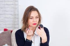 Härlig bärande skjorta för affärskvinna som håller ögonen på i spegeln med röd läppstift i händer arkivbilder