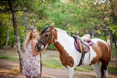 Härlig bärande tappningklänning för ung dam som rider en häst på solen Fotografering för Bildbyråer