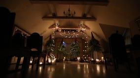 Härlig båge för julvinterbröllop på kopplingsdekorinre med stearinljus, björkjournaler, kulagirlander och gran stock video