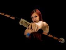Härlig bågskyttekvinna som siktar, svart bakgrund arkivbilder