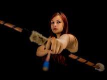 Härlig bågskyttekvinna som siktar, svart bakgrund arkivfoto