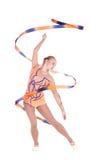 Härlig böjlig flickagymnast med ett gymnastiskt band över whi fotografering för bildbyråer