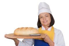Härlig bagare Holding Fresh Bread för ung kvinna med kniven över Royaltyfri Bild
