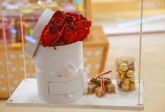 Härlig bakgrund för dag för valentin` s Röda rosor i en korg och choklader på ett träbräde royaltyfria foton