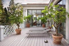 Härlig balkong med sunbeds och växter med härlig sikt av Arkivfoto