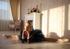 Härlig ballerina för ung kvinna som sträcker i hemmiljön, splittring på golv fotografering för bildbyråer