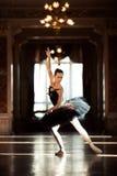 Härlig ballerinadans i en korridor med en ljuskrona mot fönstret arkivfoton