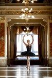 Härlig ballerinadans i en lyxig korridor mot fönstret royaltyfri fotografi