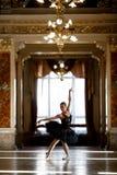 Härlig ballerinadans i en lyxig korridor mot fönstret royaltyfri bild