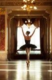 Härlig ballerinadans i en lyxig korridor mot fönstret arkivfoton