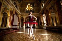 Härlig ballerinadans i en lyxig korridor i en röd klänning arkivfoto