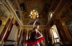 Härlig ballerinadans i en lyxig korridor i en röd klänning arkivbild