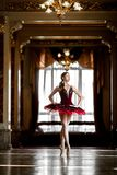 Härlig ballerinadans i en lyxig korridor i en röd klänning arkivbilder
