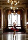 Härlig ballerinadans i en lyxig korridor i en röd klänning royaltyfri fotografi