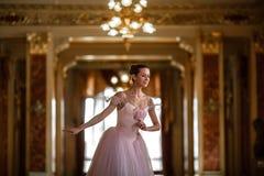 Härlig ballerinadans i en lyxig korridor i en rosa klänning royaltyfria bilder
