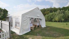 Härlig bankettkorridor under ett tält för ett bröllopmottagande royaltyfria bilder