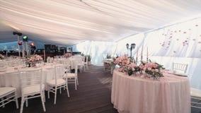 Härlig bankettkorridor under ett tält för ett bröllopmottagande lager videofilmer