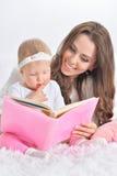 Härlig barnmoder med dotterläseboken Royaltyfria Bilder