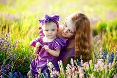 Härlig barnmoder och hennes dotter som har gyckel på lavendelfältet dagblomman ger mödrar mumsonen till arkivbild