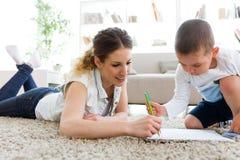 Härlig barnmoder och hennes son som hemma drar arkivbild