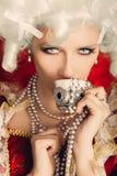 Härlig barock kvinnastående som dricker från en kopp arkivfoto