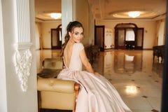 Härlig bedöva ung dam i fantastiskt klänningsammanträde på den lyxiga fåtöljen royaltyfri foto