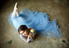 Härlig behagfull flickaballerina i en blå klänning- och pointesho arkivfoto