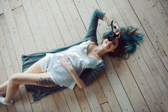 Härlig bekymmerslös ung tillfällig kvinna som ligger på trägolvet Royaltyfri Foto