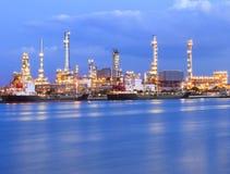 Härlig belysning av oljeraffinaderibranschväxten bredvid blått flodbruk för tema för industriell affär för energi Royaltyfri Foto