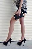 Härlig benkvinna med en svart handväskahandväska med svarta skor för höga häl Arkivbilder
