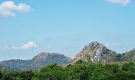 Härlig bergsikt som täckas av den gröna skogen, med moln för blå himmel och vit Naturligt landskaplandskap med bästa kopieringsut Royaltyfri Fotografi