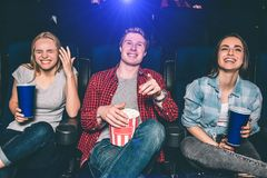 Härlig bild av lyckligt folk som skrattar i cinamekorridor De ser på skärmen och att le Flickor och grabbblick Arkivfoto