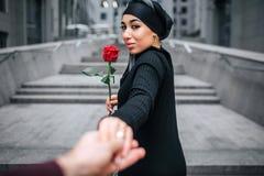 Härlig bild av rosen och blicken för ung arabisk kvinnahåll den röda tillbaka Hon luktar det Modellera hållhanden Hon ler royaltyfri foto