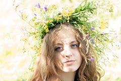 Härlig blåögd ung kvinna med en gjord färgrik girland fotografering för bildbyråer