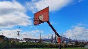 Härlig blå himmel med vita moln, gammalt rött rostigt basketbeslag i Zenica arkivbilder