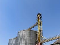 Härlig blå himmel och stora behållare i fabrik Arkivbild