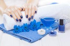 Härlig blå manikyr med krysantemumet och handduk på den vita trätabellen Spa royaltyfria foton