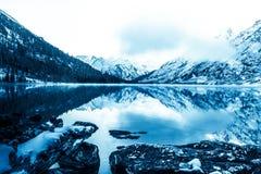 Härlig blå sjö i bergen Plan spegelyttersida av vattnet under molnen arkivbild